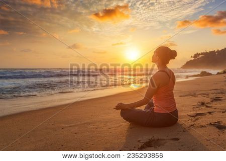 Woman doing yoga - meditate and relax in Padmasana Lotus asana pose with chin mudra outdoors at tropical beach on sunset with dramatic sun
