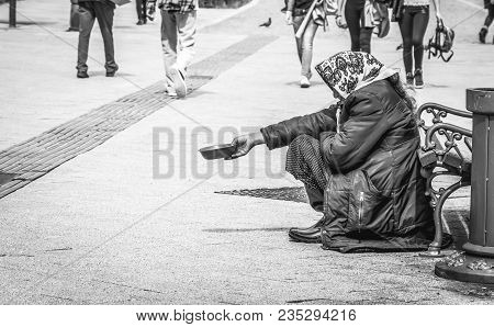 Homeless Beggar. Hungry Homeless Beggar Woman Beg For Money On The Urban Street In The City From Peo