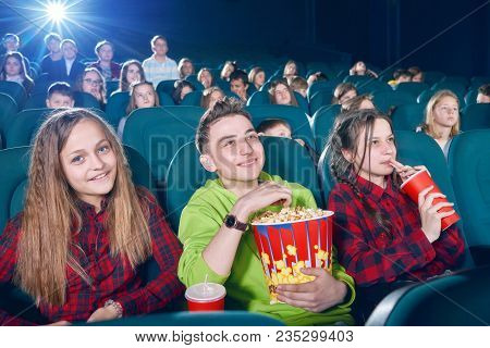 Frontview Of Happy Children Eating Popcorn By Watching Movie. Girl Drinking Fizzy Drink From Red Can