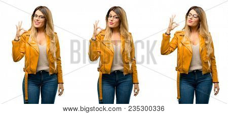 Beautiful young woman doing ok sign with hand, approve gesture over white background
