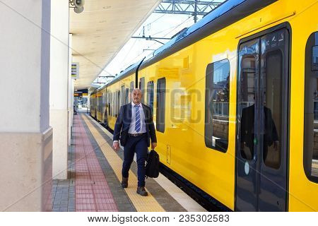 The Conductor Walks Along The Platform Next To The Yellow Train With Black Windows And Door. Europea
