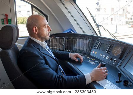 Portrait Of Middle Aged Man Driving The Modern Train In Europe