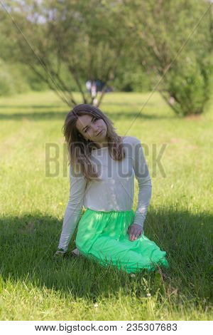 Slender Girl On Grass In Summer Park