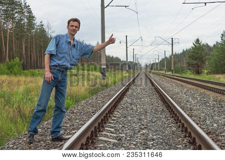 Young Man Trying To Stop A Train On A Railway