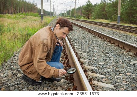 Young Man Examines The Rail Surface