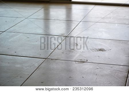 Dirty Footprints On White Tile On The Floor. Dirty Dusty Floor