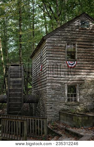 Old Wood And Stone Grist Mill With Water Wheel.