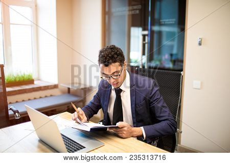 Successful Businessman Reading Information In Notepad While Sitting At The Table With Laptop Compute