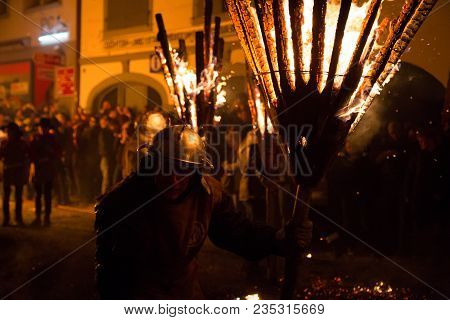 Liestal, Switzerland - March 09, 2014: Photgraph Of A Man Holding A Burning Broom Stick At The Tradi
