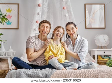 Happy family. Child daughter with father and mother. Mum, dad and girl laughing. Holiday and togetherness.