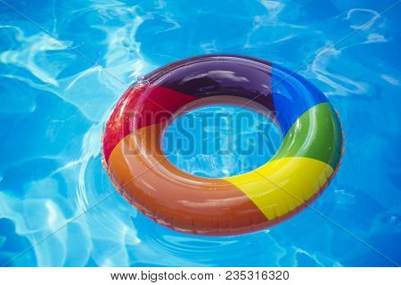 Colorful Swim Ring Or Lifebuoy. Inflatable Ring Float In Pool Blue Water. Summer Vacation And Travel