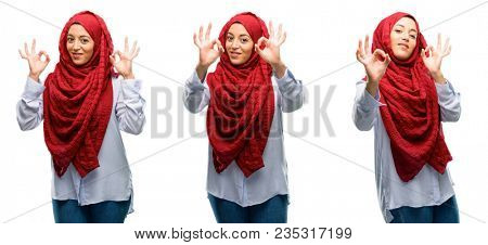 Arab woman wearing hijab doing ok sign gesture with both hands expressing meditation and relaxation isolated over white background