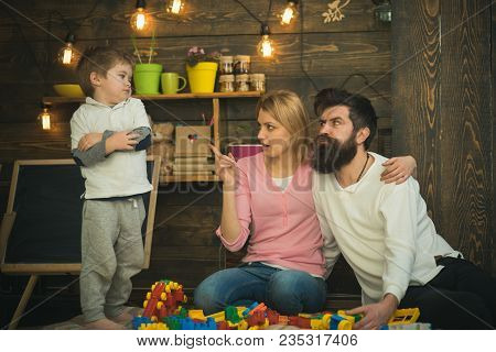 Kid With Parents Play With Plastic Blocks, Build Construction. Father, Mother And Cute Son Play With