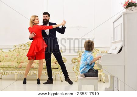 Musician Education Concept. Boy Adorable Try To Play Piano Musical Instrument, While Parents Dancing