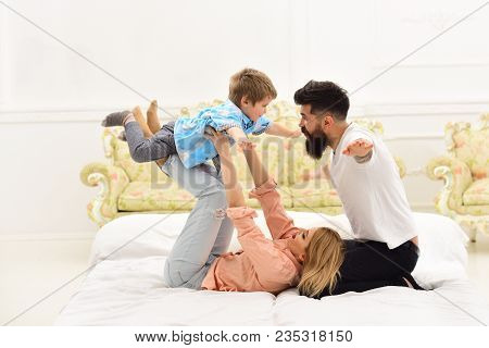 Parents With Happy Faces Pay Attention To Kid, Play Like Plane. Mother And Father Play With Cute Son