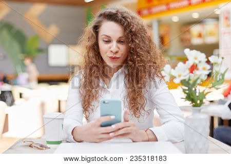 Positive Beautiful Female With Curly Bushy Hair Holds Cell Phone Surfes Internet On Modern Cell Phon