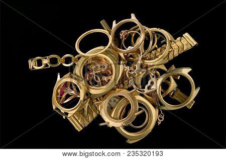 A Scrap Of Gold. Old And Broken Jewelry, Watches Of Gold And Gold-plated Isolated On A Black Backgro