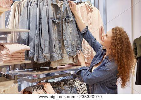 Photo Of Female Shopaholic Chooses New Denim Jacket, Likes Stylish Fashionable Clothing, Makes Shopp