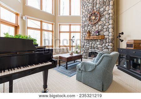 Upscale Living Room.  Inviting Scene With Piano, Floor To Ceiling Fireplace, And Modern Decor.