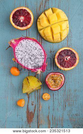 Exotic Fruits (mango, Passion Fruit, Carambola, Orange, Kumquat, Dragon Fruit) On A Blue Wooden Back