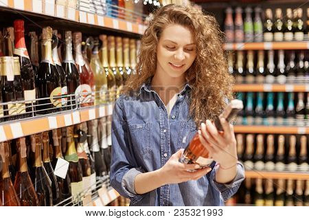 Horizontal Shot Of Gorgeous Attractive Female With Curly Hair Chooses Alcoholic Drink For Party, Rea