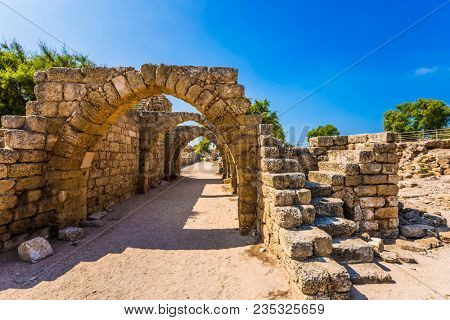 Sunny spring day. Picturesque ruins of the ancient city of Caesarea. Arched passage - covered street of Port of Caesarea. Israel. Concept of ecological and historical tourism