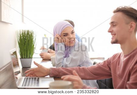 Muslim student with classmate in library