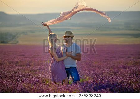A Loving Couple Walks In The Field Of Lavender, Dreams And Smiles. They Are Happy Together And Love