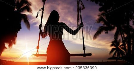 Silhouette type image of a young woman on a sunset beach