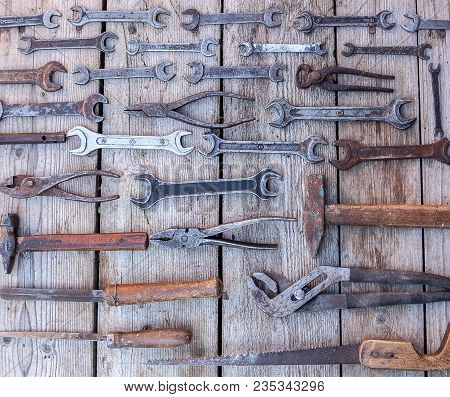 Metal Wrench Rusty Tools Lying On A Black Wooden Table. Hammer, Chisel, Hacksaw, Metal Wrench. Dirty