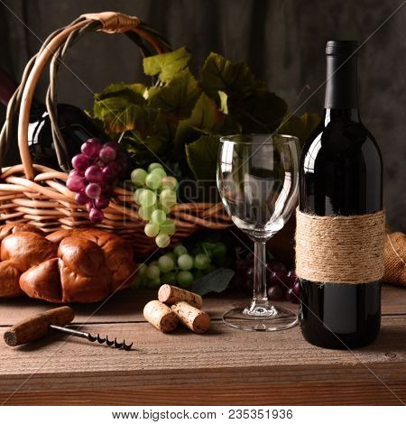 Wine Still Life: An old fashioned cork screw, a basket of grapes and leaves, a loaf of bread and some corks and an empty wineglass round out the scene.