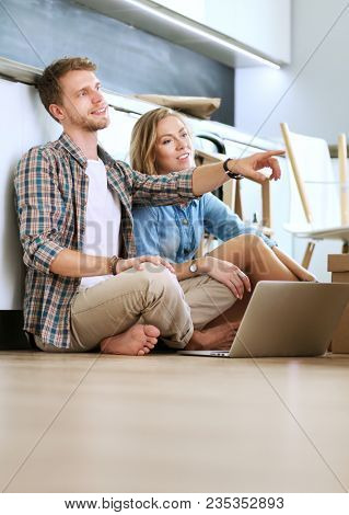 Young couple moving in new home.Sitting and relaxing after unpacking.Looking something on laptop. Young couple
