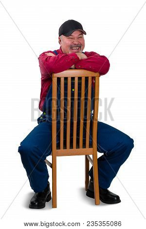 Jovial Vivacious Worker In Denim Overalls Sitting On A Reversed Wooden Chair Leaning On The Back Lau