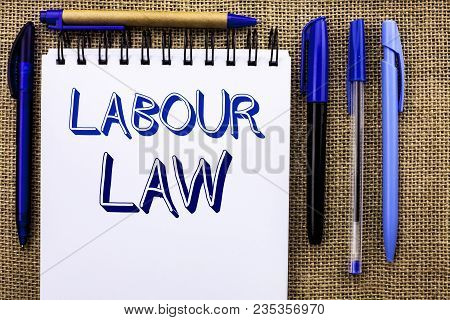Writing note showing  Labour Law. Business photo showcasing Employment Rules Worker Rights Obligations Legislation Union written Notebook Book the jute background Pens next to it. poster