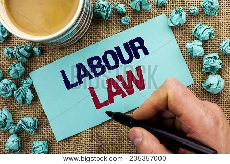 Writing note showing  Labour Law. Business photo showcasing Employment Rules Worker Rights Obligations Legislation Union written by Man Holding Pen Sticky Note Paper the jute background Cup poster