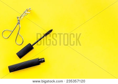 Basic Products For Eyelashes Makeup. Mascara And Eyelash Curler On Yellow Background Top View.