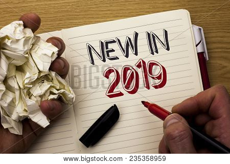 Handwriting text New In 2019. Concept meaning Fresh Era Latest Year Period Season Annual Coming Modern written by Man Notebook Book Holding Marker the wooden background Pen next to it. poster