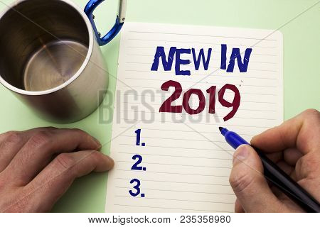 Writing note showing  New In 2019. Business photo showcasing Fresh Era Latest Year Period Season Annual Coming Modern written by Man Notebook Paper Holding Marker plain background Cup. poster