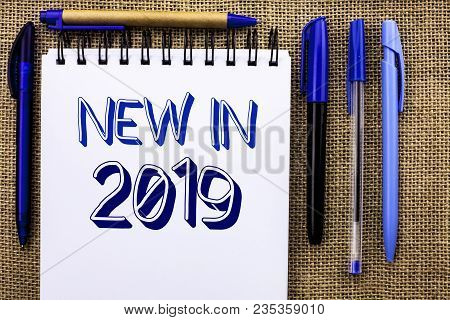 Writing note showing  New In 2019. Business photo showcasing Fresh Era Latest Year Period Season Annual Coming Modern written Notebook Book the jute background Pens next to it. poster