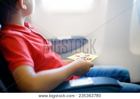 Little Kid Boy Playing Tic Tac Toe Game During Flight On Airplane. Child Sitting Inside Aircraft By