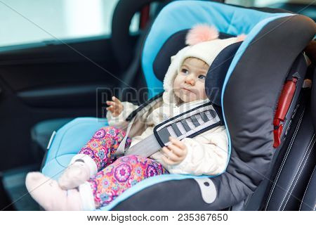 Adorable Baby Girl With Blue Eyes Sitting In Car Seat. Toddler Child In Winter Clothes Going On Fami