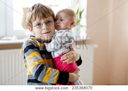 Happy Little Kid Boy With Newborn Baby Girl, Cute Sister. Siblings. Brother Holding Baby Girl On Arm