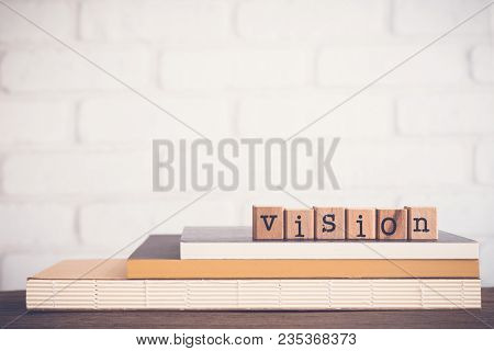 The Word Vision, Alphabet On Wooden Rubber Stamps On Top Of Books And Table. Background Copy Space,