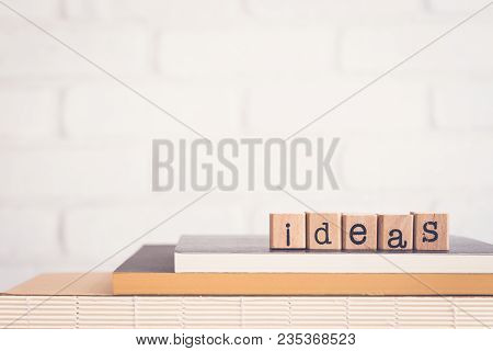 The Word Ideas, Alphabet On Wooden Rubber Stamps On Top Of Books And Table. Background Copy Space, V