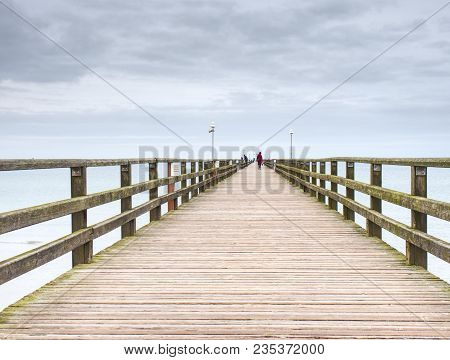Long Wooden Pier On Baltic Coast During Morning Windless. Cold Weather, Peaceful Silent Day. Empty M