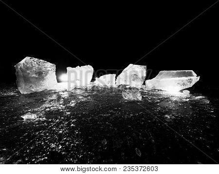 Blue Ice Cubes Shine On Flat Glacier Surface.  Thanks To Spot Light Shine Curved Details Inside Of I
