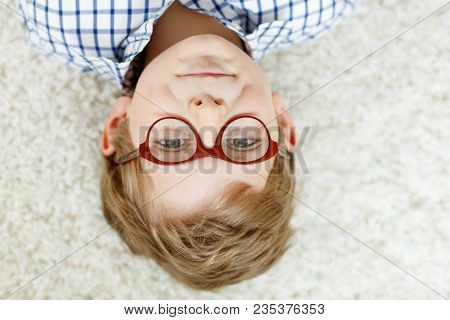 Close-up Portrait Of Little Blond Kid Boy With Brown Eyeglasses On White Background. Happy Smiling C
