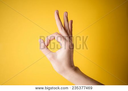 Woman Hand Pointing Up Okay, Yes, Accepting Hand Sign To The Side, Studio Isolated On Yellow Backgro