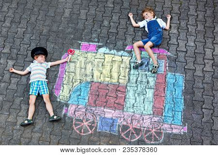 Two Little Kids Boys Having Fun With Train Or Steam Locomotive Picture Drawing With Colorful Chalks