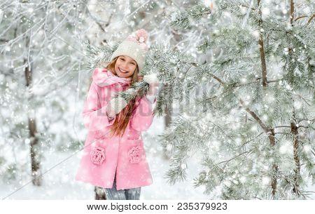 Girl outside in winter near Christmas tree